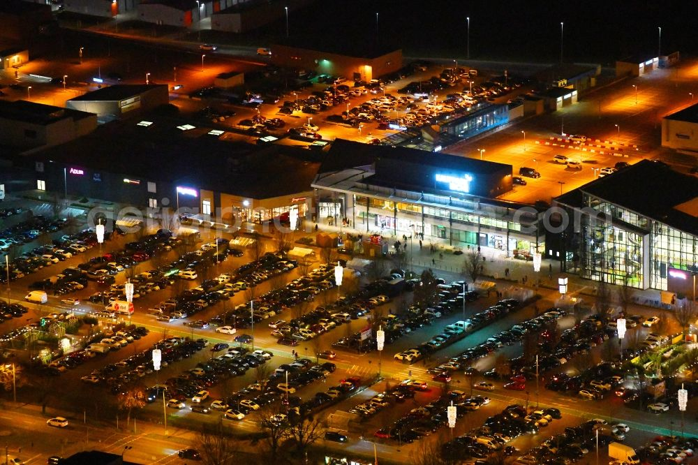 Ahrensfelde at night from the bird perspective: Night lighting building complex of the shopping center KaufPark Eiche der Unibail-Rodamco Germany GmbH in Ahrensfelde in the state Brandenburg