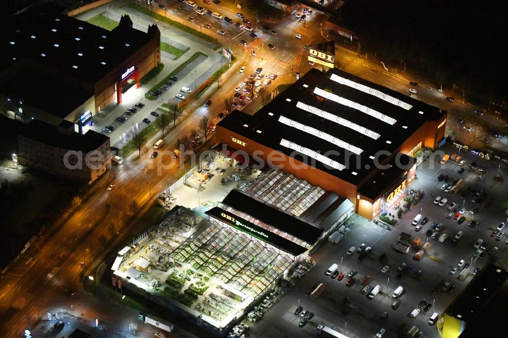 Aerial image at night Berlin - Night lighting Building of the construction market OBI Markt Berlin-Treptow on Adlergestell in the district Adlershof in Berlin, Germany.