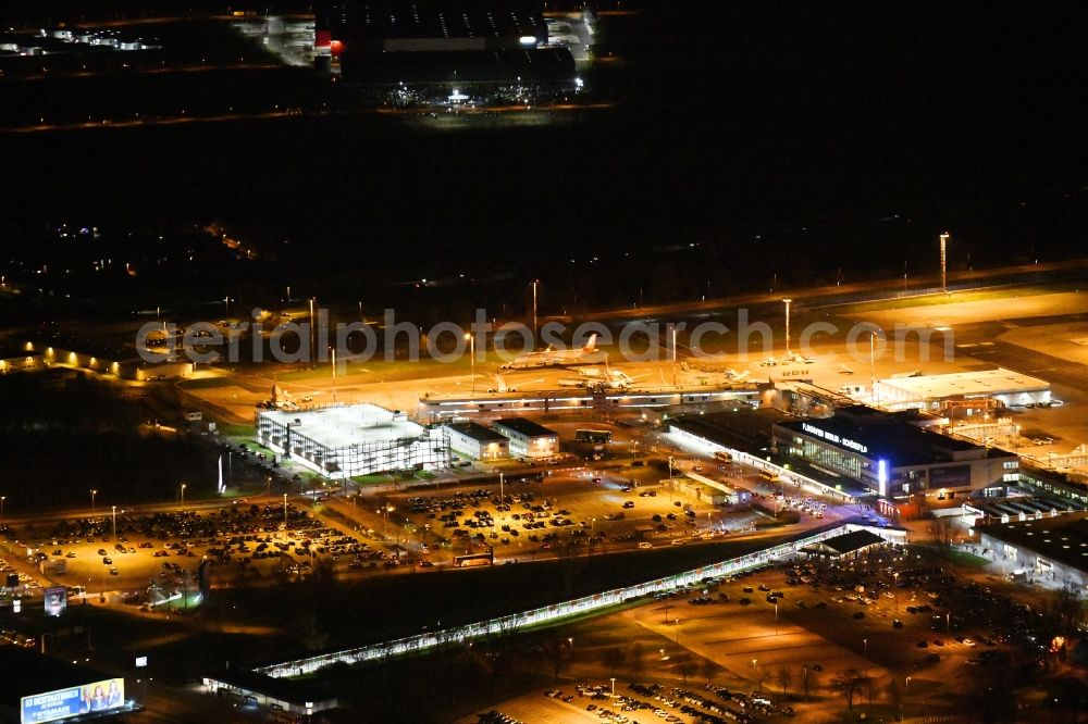 Aerial image at night Schönefeld - Night lighting Runway with hangar taxiways and terminals on the grounds of the airport Berlin-Schoenefeld in Schoenefeld in the state Brandenburg, Germany. Further information at: Flughafen Berlin Brandenburg GmbH.