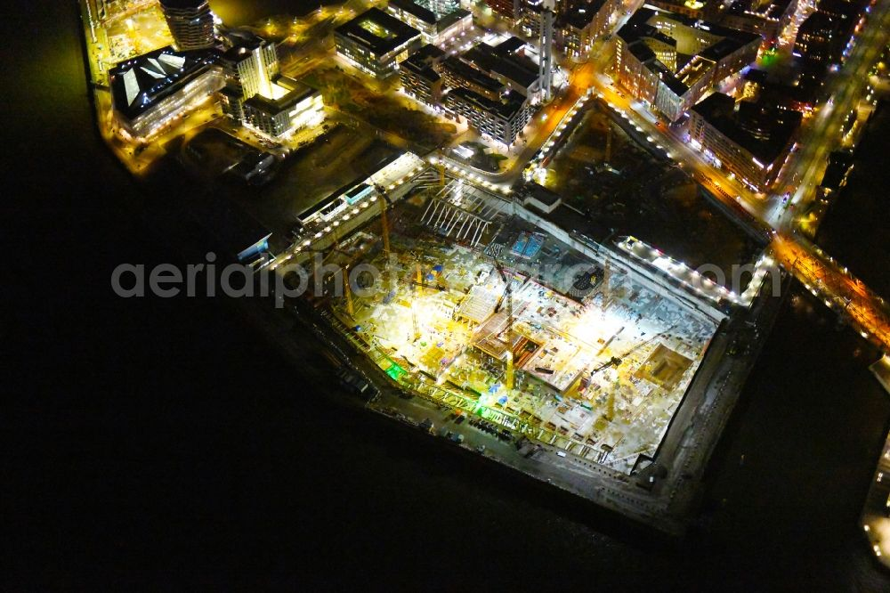 Hamburg at night from the bird perspective: Night lighting construction site for the new building complex of the shopping center at Ueberseequartier at Chicagokai - Osakaallee in the area of the former Grasbrooks in the Hafencity district in Hamburg, Germany. Further information at: CHRISTIAN DE PORTZAMPARC, Depenbrock Bau GmbH & Co. KG, F + Z Baugesellschaft, Zweigniederlassung der Hecker Bau GmbH & Co. KG, Stump GmbH, Unibail-Rodamco Germany GmbH, Unibail-Rodamco UeSQ Sued Quartiersmanagement GmbH.