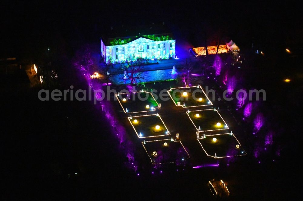 Berlin at night from the bird perspective: Night pinky lighting palace Friedrichsfelde Tierpark in the district Friedrichsfelde in Berlin, Germany