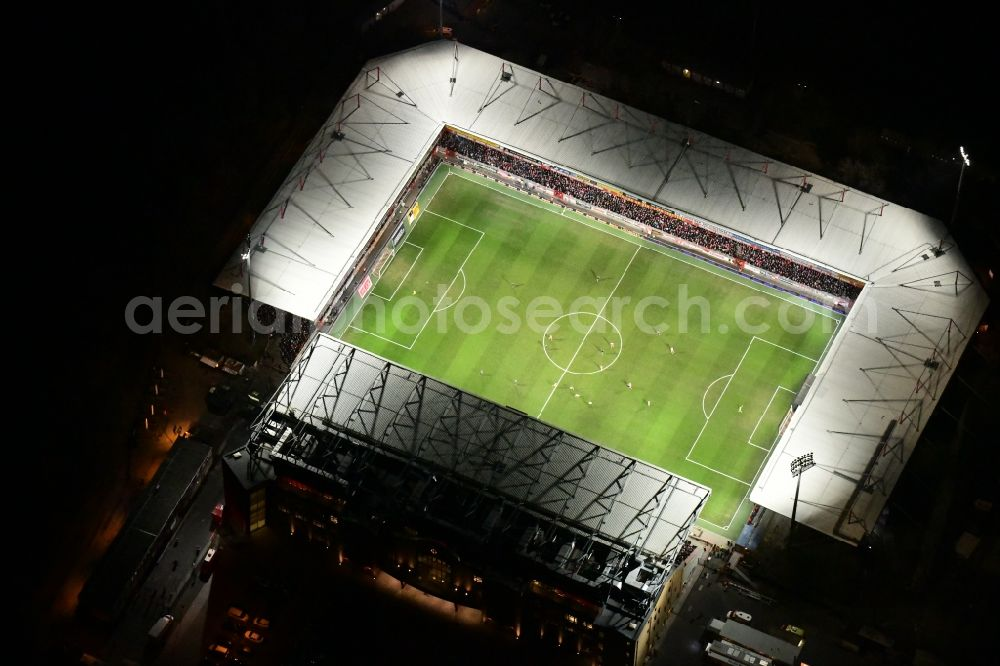 Berlin at night from the bird perspective: Night lighting view of the football stadium Alte Foersterei with its new grandstand the district of Koepenick in Berlin. The pitch is homestead for the football games of FC Union Berlin. Further information at: 1. FC Union Berlin e.V., Alte Foersterei Veranstaltungs GmbH & Co. KG, Brauer Baugesellschaft mbH & Co. KG.