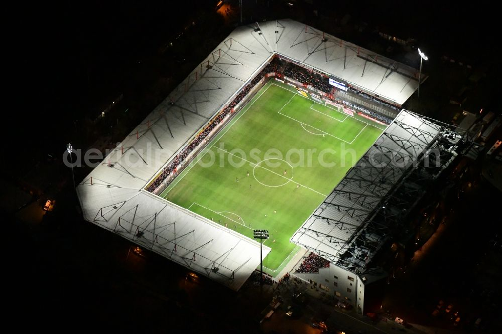 Aerial photograph at night Berlin - Night lighting view of the football stadium Alte Foersterei with its new grandstand the district of Koepenick in Berlin. The pitch is homestead for the football games of FC Union Berlin