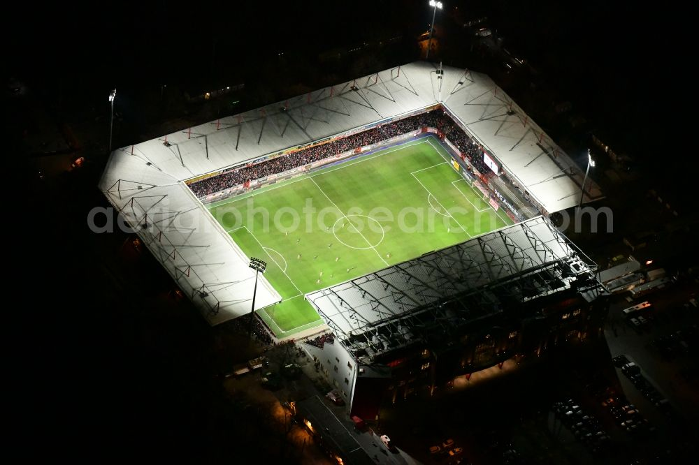 Aerial image at night Berlin - Night lighting view of the football stadium Alte Foersterei with its new grandstand the district of Koepenick in Berlin. The pitch is homestead for the football games of FC Union Berlin. Further information at: 1. FC Union Berlin e.V., Alte Foersterei Veranstaltungs GmbH & Co. KG, Brauer Baugesellschaft mbH & Co. KG.