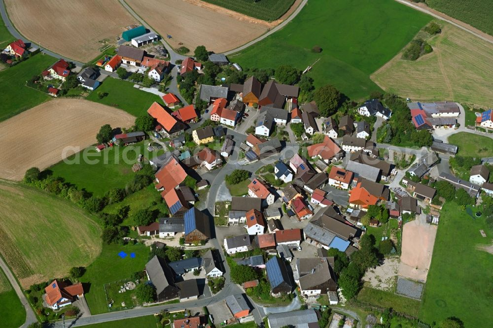Seubersdorf from the bird's eye view: Agricultural land and field borders surround the settlement area of the village in Seubersdorf in the state Bavaria, Germany