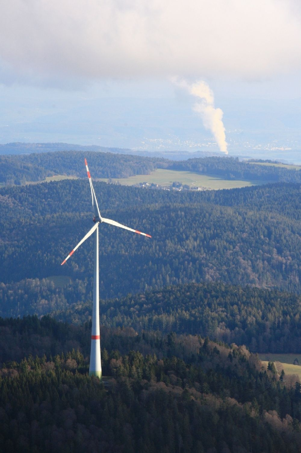 Schopfheim from the bird's eye view: Wind turbines of the wind farm Rohrenkopf in the Black Forest in Gersbach in the state Baden-Wurttemberg, Germany. In the background the steam column of swiss nuclear power plant Leibstadt KKL. Symbolic image for the controversial debate of nuclear power versus renewable power.