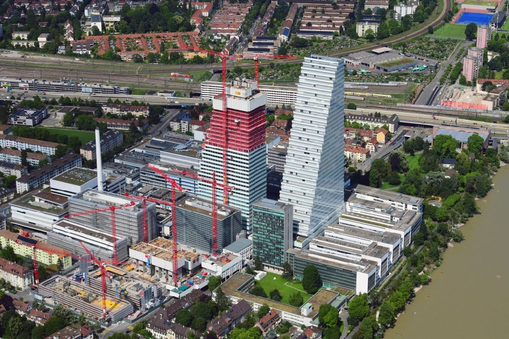 Aerial image Basel - Extension construction sites on the premises of the pharmaceutical company Roche with the cityscape-defining high-rise building in Basel in Switzerland. Construction works for the second tower are visible