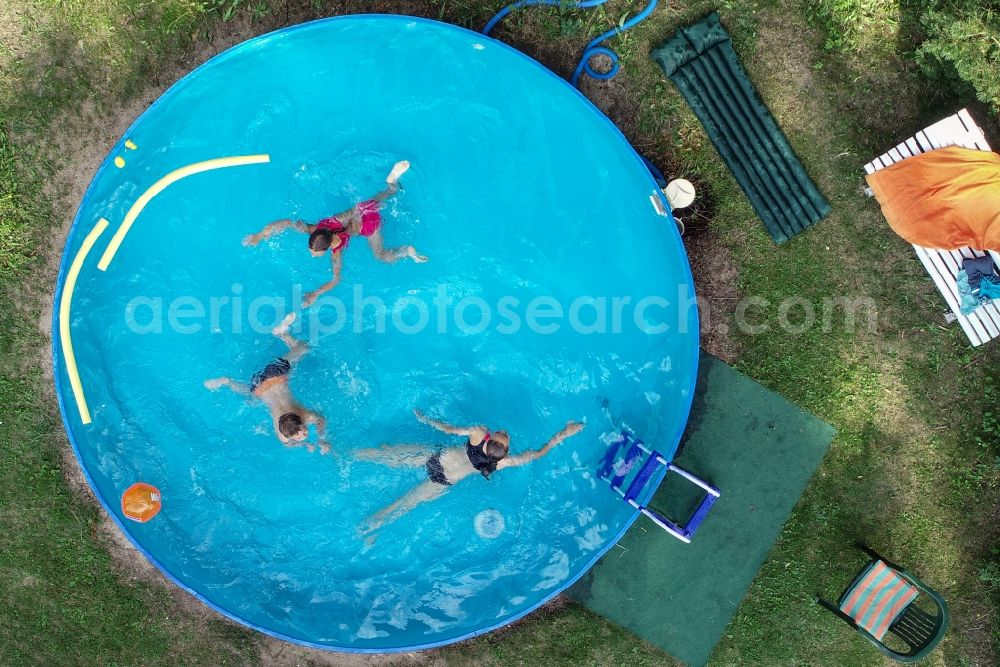 Aerial photograph Petersdorf - Refreshing swim in the blue pool - swimming pool in Petersdorf in the state Brandenburg, Germany