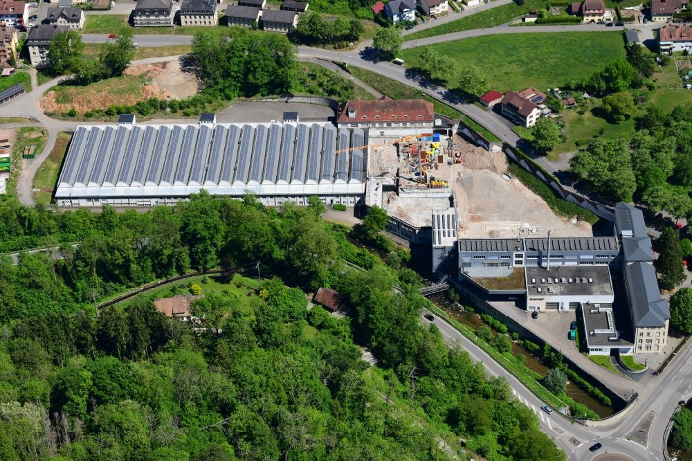 Wehr from the bird's eye view: Panel rows of photovoltaic and solar farm on the company's roof of the former textile company Brennet AG in Wehr (Baden) in the state Baden-Wurttemberg. Part of the area is prepared for new residential buildings
