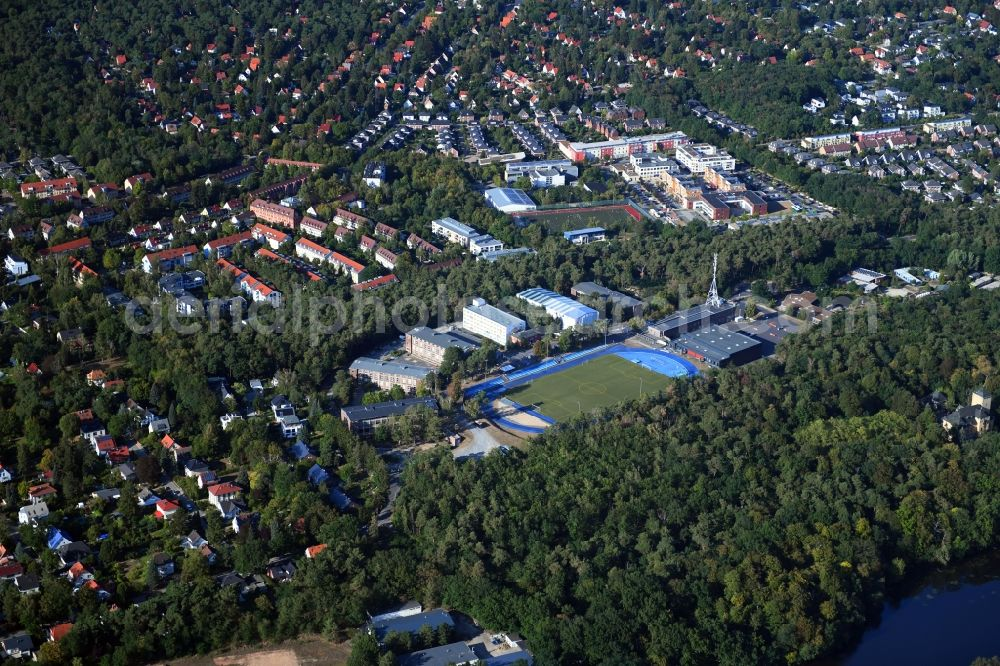 Aerial image Kleinmachnow - Sports facilities of the Berlin Brandenburg International School and residential buildings in Kleinmachnow in the state of Brandenburg. The BBIS includes a football pitch and athletics facilities in a distinct blue colour. Residential buildings and estates as well as a primary school are surrounded by trees and woods