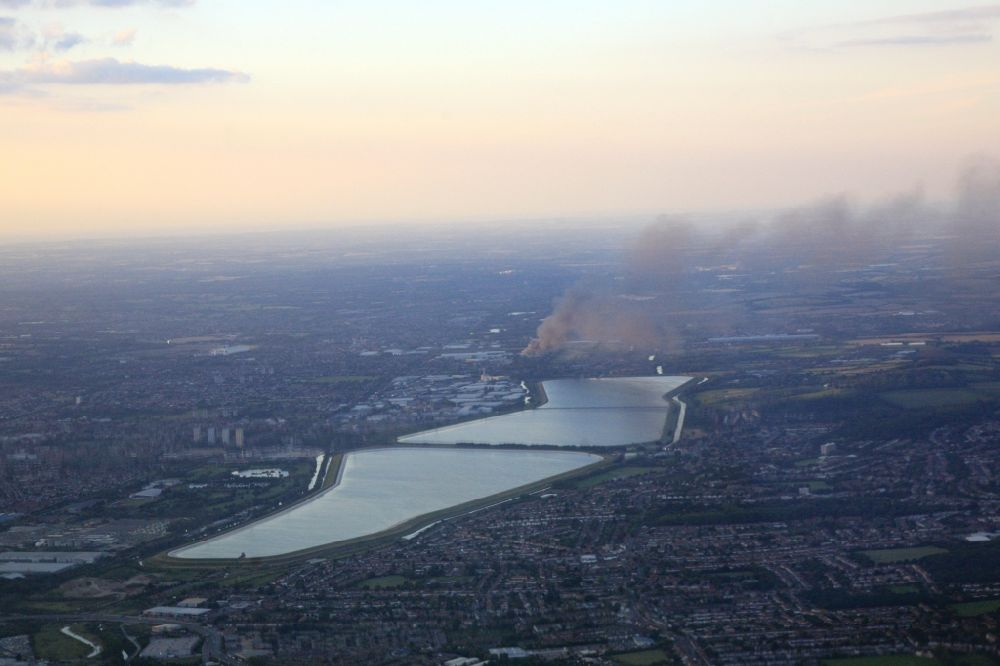 Aerial photograph Enfield Town - Riots and excesses by young people in and around London set houses and warehouses on fire. Columns of smoke rising into the evening sky. Viewed from an airliner, departet at London City airport