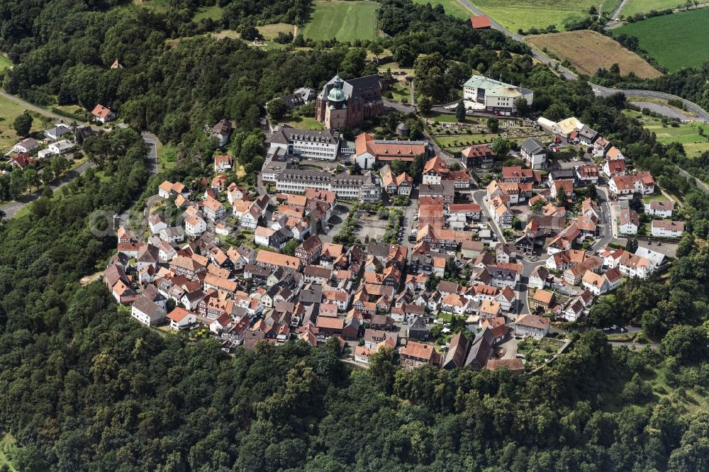 Amöneburg from the bird's eye view: Surrounded by forest and forest areas center of the streets and houses and residential areas in Amoeneburg in the state Hesse, Germany