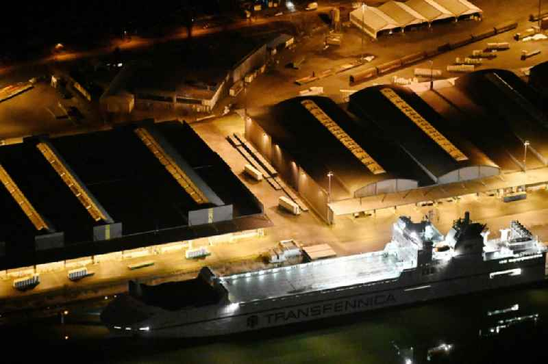 Night lighting warehouse complex-building in the industrial area on the banks of the River Trave at Fabrikstrasse overlooking an anchored cargo ship in Luebeck in the state Schleswig-Holstein