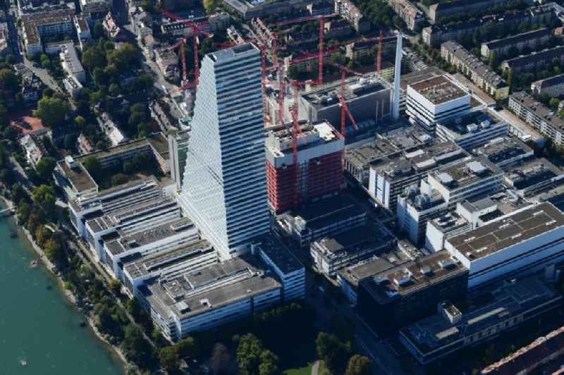 Extension construction sites on the premises of the pharmaceutical company Roche with the cityscape-defining high-rise building in Basel in Switzerland. Construction works for the second tower are visible. Further information at: Amstein + Walthert AG,  Drees & Sommer SE,  Herzog & de Meuron.