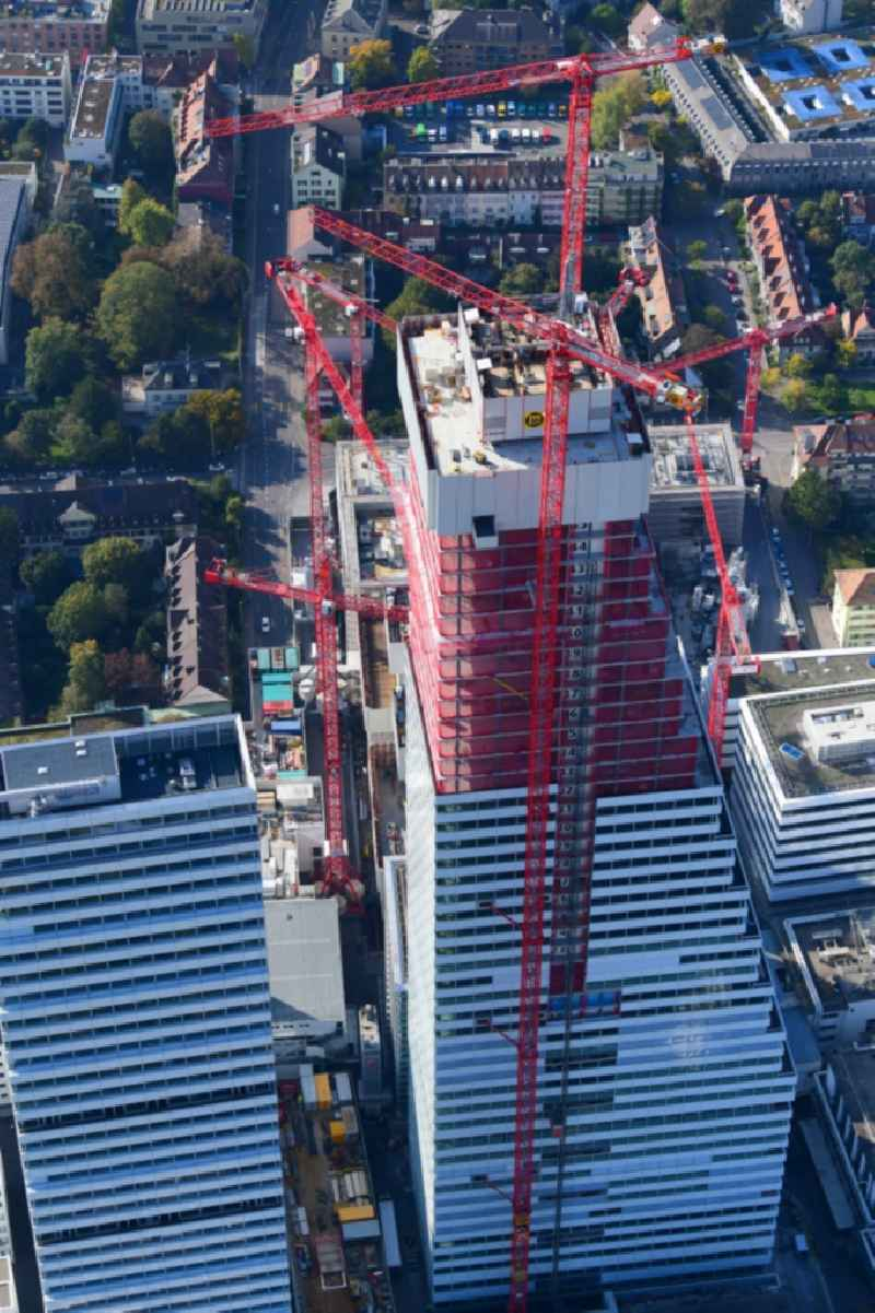 Extension construction sites on the premises of the pharmaceutical company Roche with the cityscape-defining high-rise building in Basel in Switzerland. Construction works for the second tower are visible
