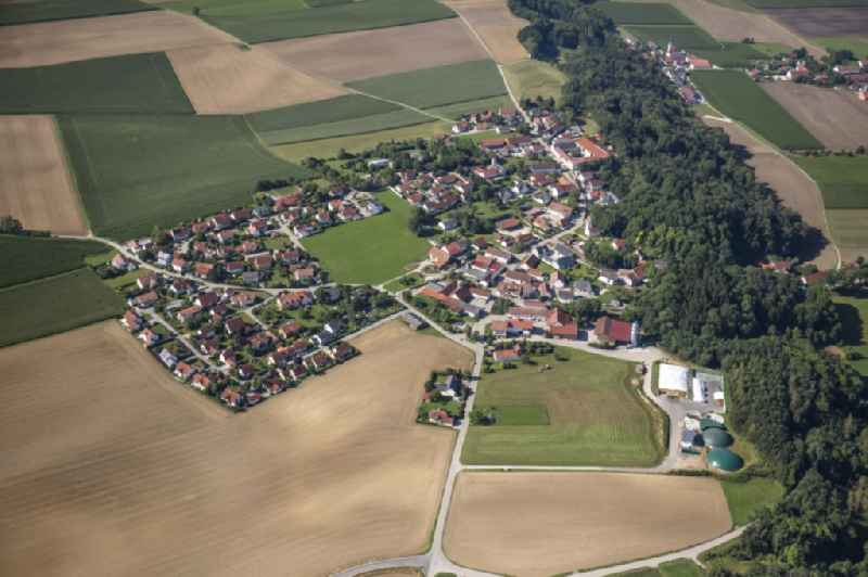 Agricultural land, fields and forest surround the settlement area of a??a??the village in Berghofen in the state Bavaria, Germany