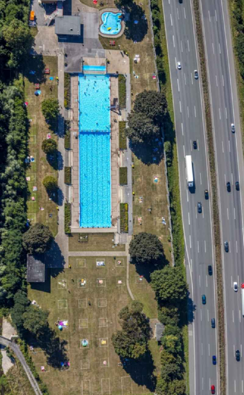 Bathers on the lawn by the pool of the swimming pool ' Stenkhoff-Bad ' in Bottrop in the state North Rhine-Westphalia, Germany