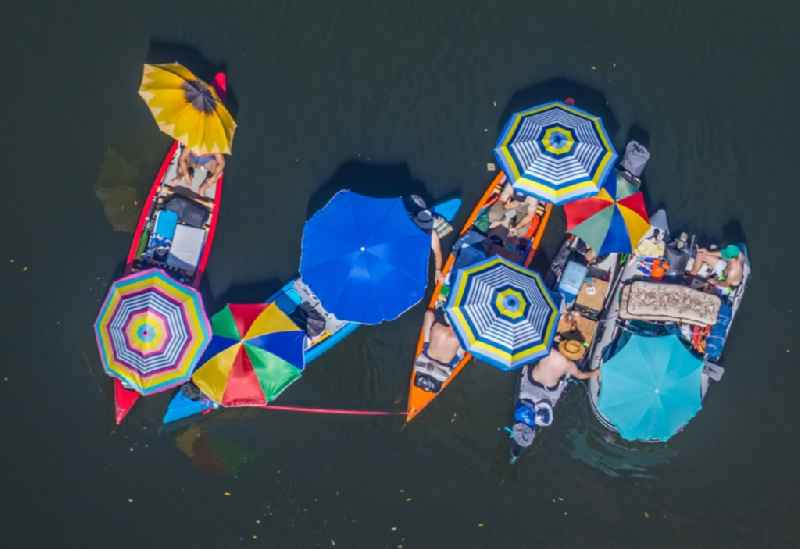 Colorful picnic under parasols in boats on the water wall on the Lippe in the district of Hervest in Dorsten in the state North Rhine-Westphalia, Germany