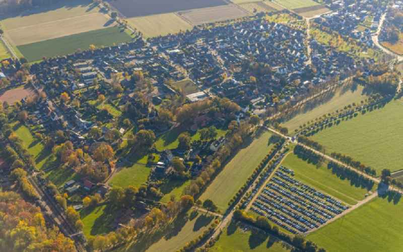 Village view on the edge of agricultural fields and land with parking for cars from Movie Park Bottrop at the 'Halloween Horror Festival 2020' on Gruener Weg in Feldhausen in the state North Rhine-Westphalia, Germany