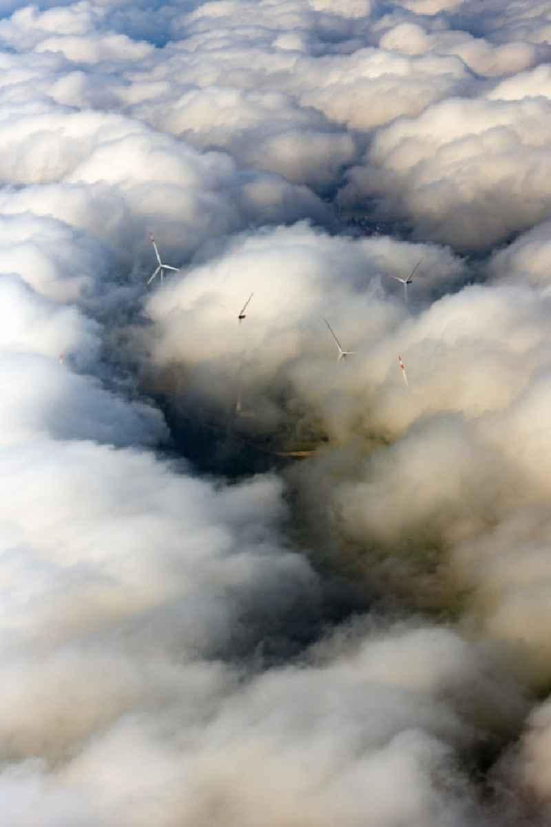 Weather-induced wind energy installations embedded in a clouds layer in Flachslanden in the state Bavaria, Germany.