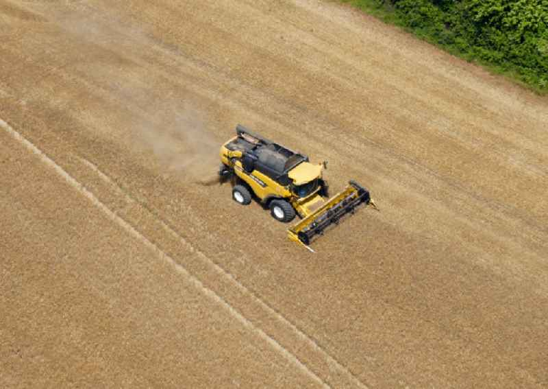 Harvest use of heavy agricultural machinery - combine harvesters and harvesting vehicles on agricultural fields in Geismar in the state Lower Saxony, Germany