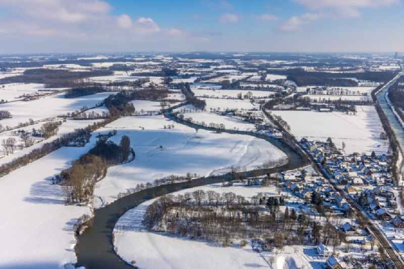 Wintry snowy meandering, serpentine curve of river Lippe in the field landscape along the Lippestrasse in the district Heessen in Hamm at Ruhrgebiet in the state North Rhine-Westphalia, Germany