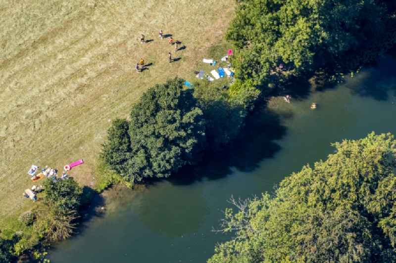 Bathers look to cool off in summer on the banks of the river of Lippe in Heessen in the state North Rhine-Westphalia, Germany