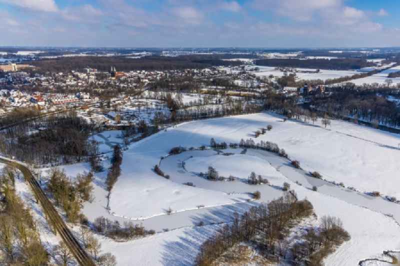 Wintry snowy curved loop of the riparian zones on the course of the river ' Muehlengraben ' in Hamm-Heessen in the state North Rhine-Westphalia, Germany