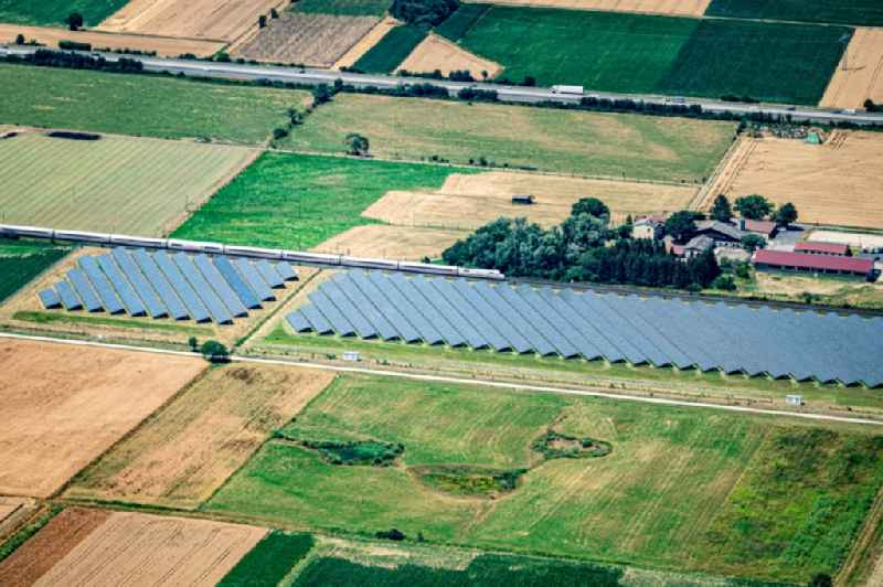 Panel rows of photovoltaic and solar farm or solar power plant along the Bahn Rheintal Strecke in Hohberg in the state Baden-Wurttemberg, Germany