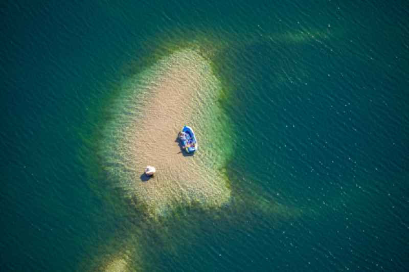 Sport Boat - Dinghy on the water surface on a sandbank on the Tenderingssee in Huenxe in the state North Rhine-Westphalia, Germany