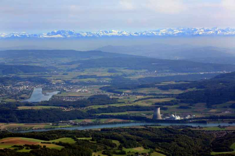 Reactor unit and cooling Tower of the NPP  nuclear power plant Leibstadt in Leibstadt in the canton Aargau, Switzerland. Looking from Germany over the river Rhein to the mouth of Aare and the summits of Swiss Alps