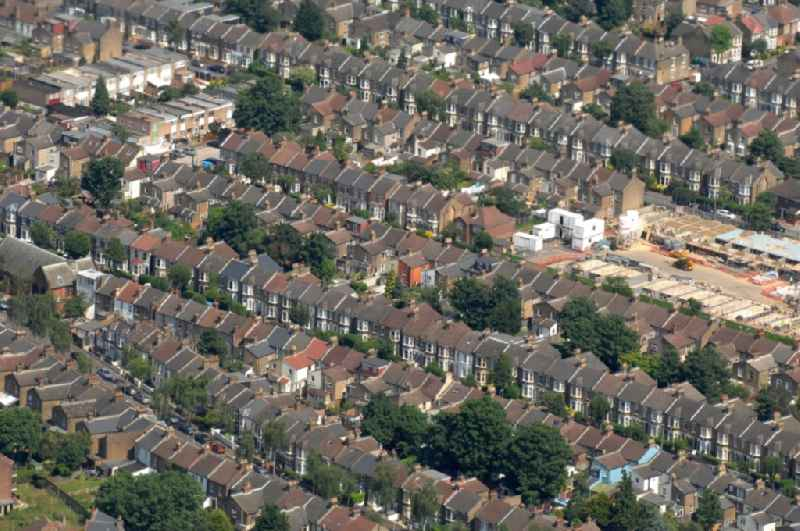 View of a row of terraced houses with single-family homes between Albert Road and Scott's Road in the district Leyton in London  in the county of Greater London in the UK