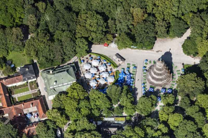 The Chinese Tower beer garden in English Garden in Munich Schwabing in the state Bavaria. In high summer temperatures hardly any guests can be seen at the tables and benches in the sun. The restaurant is set for a celebration