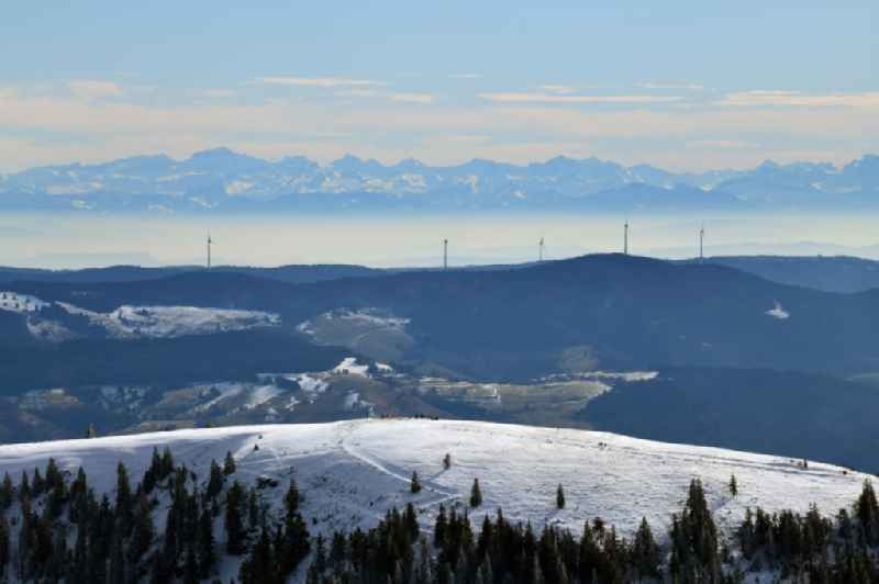 Wintry snowy mountainous landscape of the mountain summit Belchen in the Black Forest in Muenstertal/Schwarzwald in the state Baden-Wurttemberg, Germany. Looking over the wind park Rohrenkopf with the 5 wind energy plants to the mountain range of the Alps