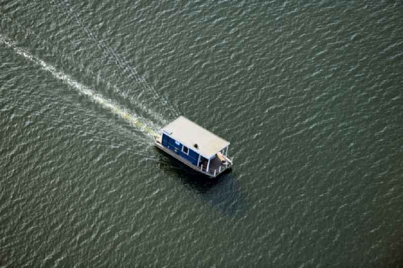 Houseboat in motion on the water surface on Breitlingsee in Neuendorf in the state Brandenburg, Germany