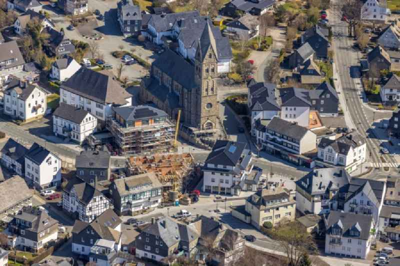 Construction site for the multi-family residential building on Bahnhofstrasse - Kirchstrasse overlooking the church building of the 'Pfarrkirche Sankt Nikolaus' in Olsberg in the state North Rhine-Westphalia, Germany