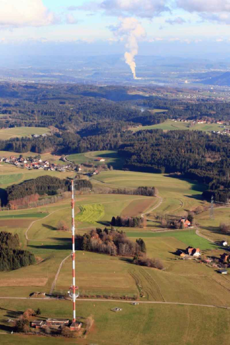 Radio tower and transmitter on the plateau of the Hotzenwald in the Black Forest in district Bergalingen in Rickenbach in the state Baden-Wurttemberg, Germany. In the background the steam column of nuclear power plant Leibstadt in Switzerland.