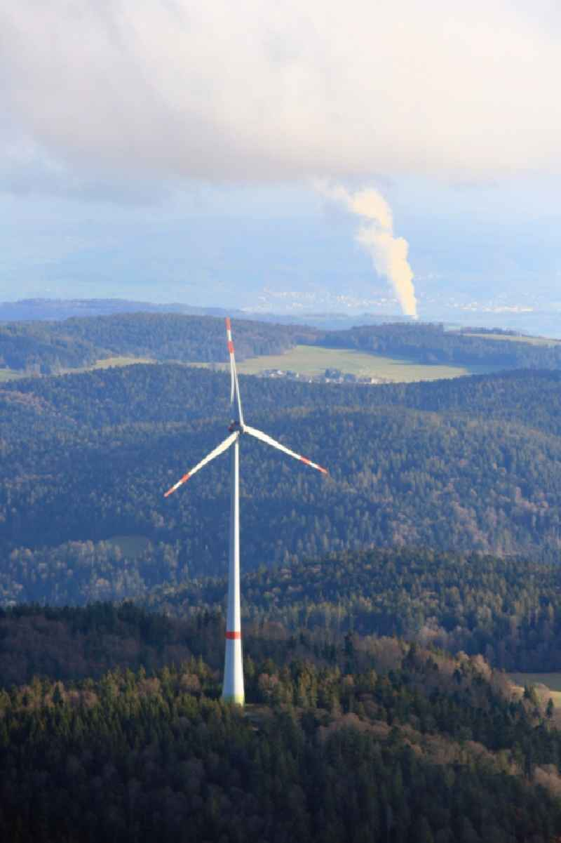 Wind turbines of the wind farm Rohrenkopf in the Black Forest in Gersbach in the state Baden-Wurttemberg, Germany. In the background the steam column of swiss nuclear power plant Leibstadt KKL. Symbolic image for the controversial debate of nuclear power versus renewable power.