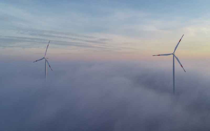 Weather-induced wind energy installations embedded in a fog layer in Sieversdorf in the state Brandenburg, Germany