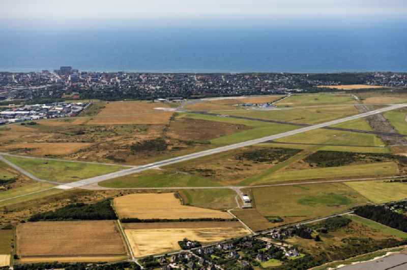 Runway with hangar taxiways and terminals on the grounds of the airport Sylt on Sylt with the town center of Westerland in the state Schleswig-Holstein