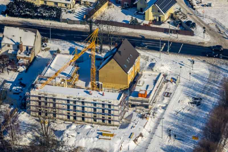 Wintry snowy construction site for the new building on Kamener Strasse corner Hallohweg in Unna at Ruhrgebiet in the state North Rhine-Westphalia, Germany
