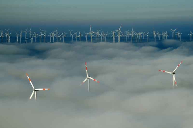 Weather-induced wind energy installations embedded in a fog layer on a field in Waltersdorf in the state Brandenburg, Germany