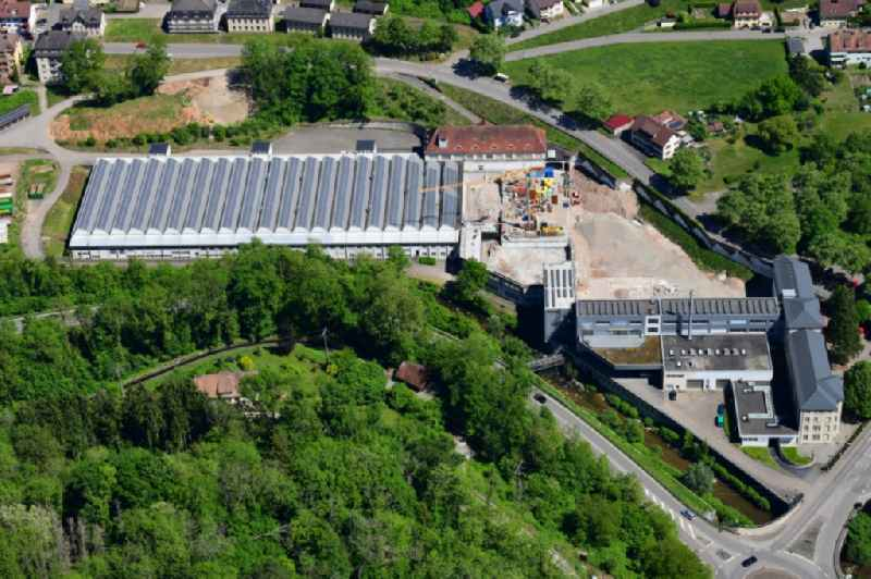Panel rows of photovoltaic and solar farm on the company's roof of the former textile company Brennet AG in Wehr (Baden) in the state Baden-Wurttemberg. Part of the area is prepared for new residential buildings