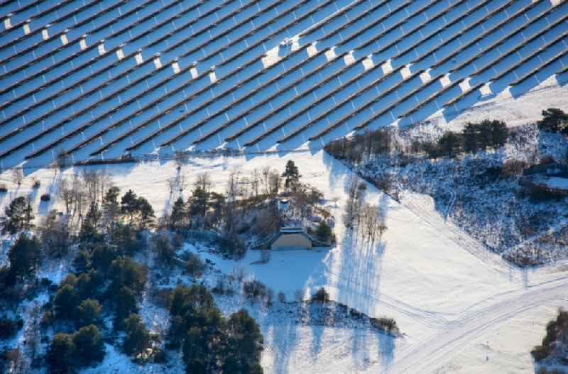 Wintry snowy solar power plant and photovoltaic systems on airfield in Werneuchen in the state Brandenburg, Germany