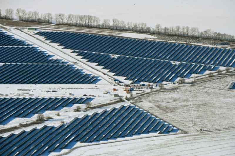 Wintry snowy construction site and assembly work for solar park and solar power plant ' Solarpark Weesow-Willmersdorf ' in Willmersdorf in the state Brandenburg, Germany