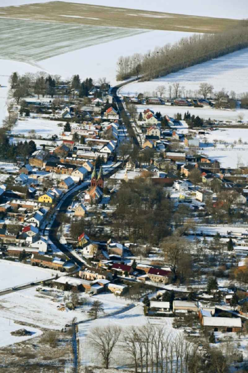 Wintry snowy agricultural land and field boundaries surround the settlement area of the village in Willmersdorf in the state Brandenburg, Germany