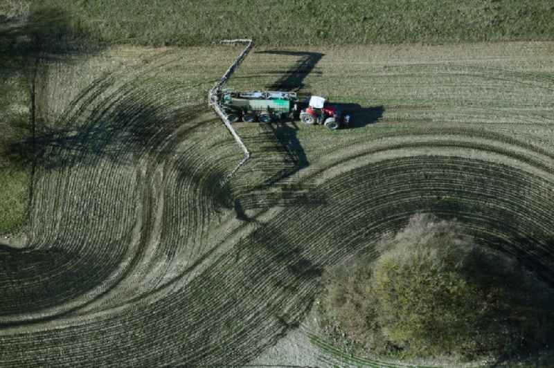 Vertical aerial view from the satellite perspective of the spraying manure as fertilizer with tractor and tank trailer on agricultural fields in Kaltenwestheim in the state Thuringia, Germany