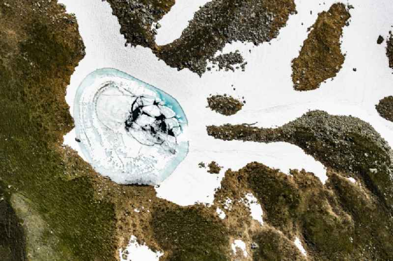 Vertical aerial view from the satellite perspective of the wintry snowy snowmelt water accumulation in a massif of the Alps in Mittersill in Tirol, Austria