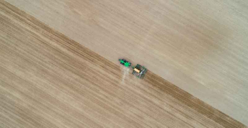 Vertical aerial view from the satellite perspective of the cultivation of a field using a tractor with agricultural machine for sowing in Seelow in the state Brandenburg, Germany