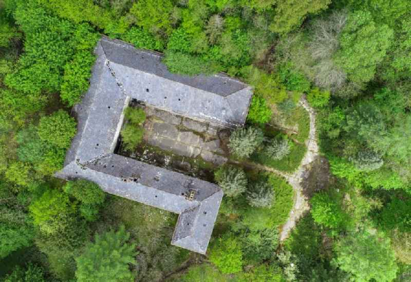 Vertical aerial view from the satellite perspective of the ruin of the decaying building structure of the former forester's house in Treppeln in the state Brandenburg, Germany